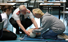 Commissioner assisting at first aid course